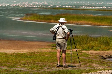 observing: Tourist observing birds and taking photos by the lake