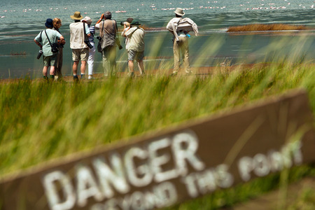 Senior tourists on photo safari in Africa in danger zone