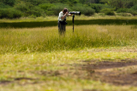 tele: Wildlife photographer in the field taking photos with monopod and tele lens Stock Photo
