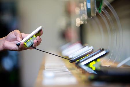 Oppakken van een mobiele telefoon van een plank in een winkel Stockfoto