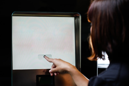 automatic teller machine bank: Woman touching the screen of vending machine
