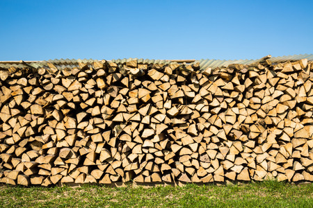 front or back yard: Pile of chopped firewood with green grass and blue sky
