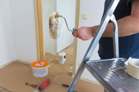 Man holding roller while renovating home photo