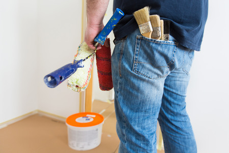 man painting: Man holding rollers and brushes while renovating home Stock Photo