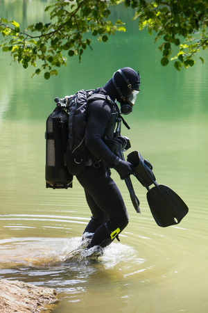 cilinder: Scuba diver with full face mask entering lake