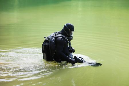 cilinder: Scuba diver wearing full face mask entering lake