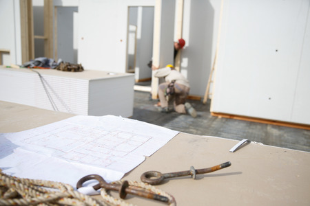 Building plan and eye bolt in focus with workers at construction site Stock Photo