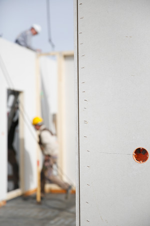 bare wire: Electricity sockets in a drywall with tubing for wires and workers in background