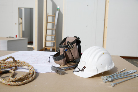 proffessional: Building equipment, hardware and building plan: helmet, hammer, rope, screws,workers tool bag Stock Photo