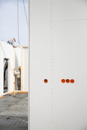 bare wire: Electricity sockets in a drywall with tubing for wires and workers in the background Stock Photo