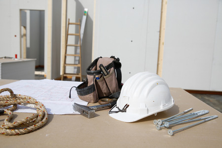 wooden house: Building equipment, hardware and building plan: helmet, hammer, rope, screws,worker Stock Photo