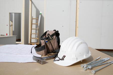 libel: Building equipment, hardware and building plan: helmet, hammer, screws,worker Stock Photo