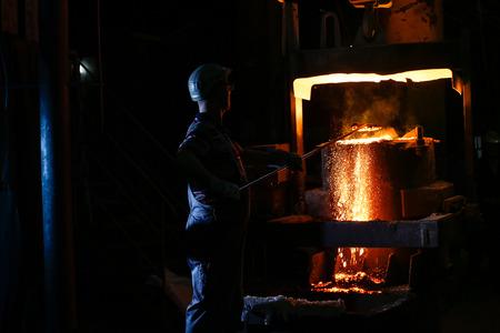 A founder holding a crucible of molten cast iron Stock Photo
