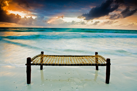 sea bed: Bed on a sandy beach touching the sea under dramatic sky