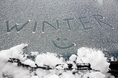 Word \winter\ and a smiley drawn on snowy car windshield photo