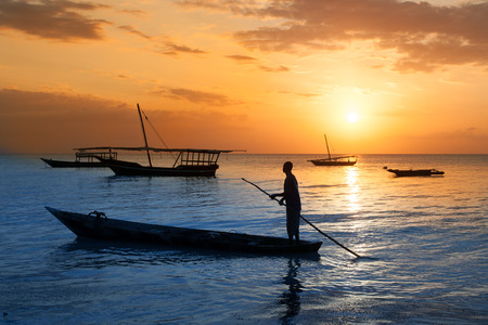 africa sunset: Man on a traditional boat off the coast of Zanzibar at sunset