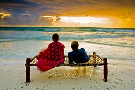 day bed: A romantic couple on honeymoon enjoying a breathtaking scene on a tropical beach in Zanzibar, Africa Stock Photo