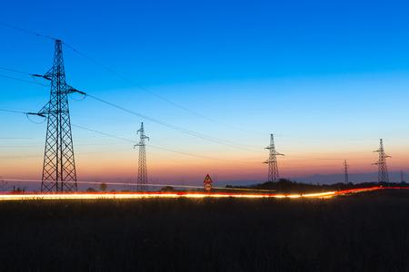 redes electricas: Pilones y líneas de energía eléctrica en la oscuridad con semáforo frente