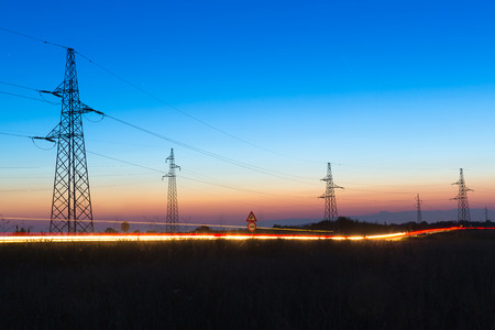 Pylons and electrical power lines at dusk with traffic lights in front
