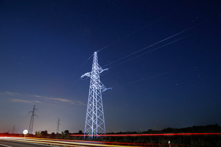 electric grid: Pylon for electricity distribution at night with car lights in front Stock Photo