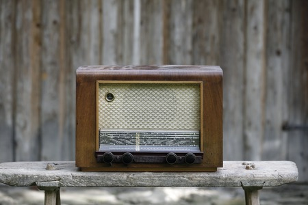 semi conductor: Old-fashioned vintage radio on a wooden bench Stock Photo