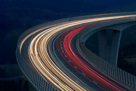 Blurred lights of vehicles driving on a tall viaduct with wind barriers, long exposure Stockfoto