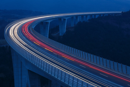 Blurred lights of vehicles driving on a tall viaduct with wind barriers, long exposure Imagens