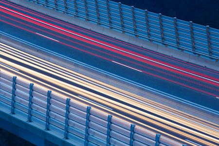 Blurred lights of vehicles driving on a viaduct with wind barriers, long exposure Stok Fotoğraf