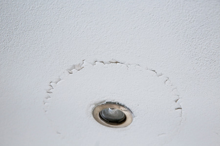 A cracked ceiling with peeling layer due to water leak. LED light. photo