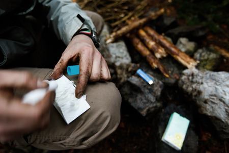 outdoor lighting: Man lighting a fire with help of a lip balm Stock Photo