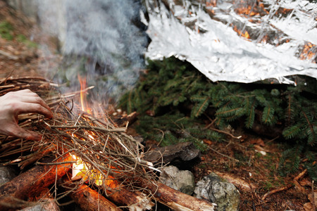 forest fire: Man lighting a fire after preparing emergency shelter for the night