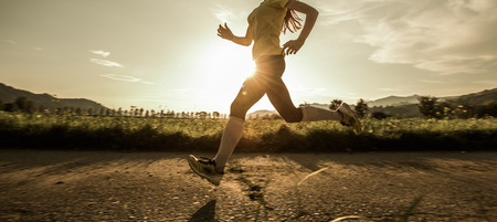 capable: Fit woman running fast, training in bright sunshine Stock Photo