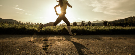 run: Fit woman running fast, training in bright sunshine Stock Photo