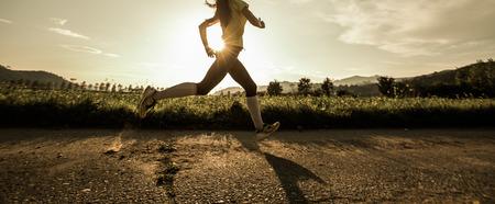 Mujer apta correr rápido, la formación en el sol brillante