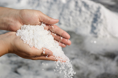 Woman scattering a pile of freshly harvested salt
