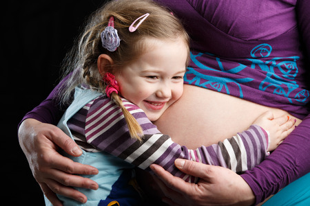 kids hugging: Adorable little girl embracing the belly of a highly pregnant mother, in expectation of a sibling