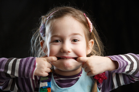 joking: Adorable little girl making faces for the camera, black background