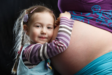 sibling: Adorable little girl embracing the belly of a highly pregnant mother, in expectation of a sibling