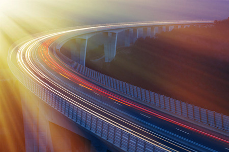 Blurred lights of vehicles driving on a tall viaduct with wind barriers, long exposure, sunlit with golden rays. Morning traffic.