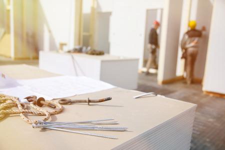 materiales de construccion: La construcci�n de plan, perno de ojo y los tornillos en los paneles de cart�n yeso con los trabajadores en el fondo