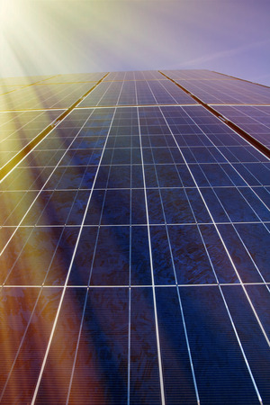 renewable energy resources: Solar panels and blue sky with sunlight shining on the panels Stock Photo