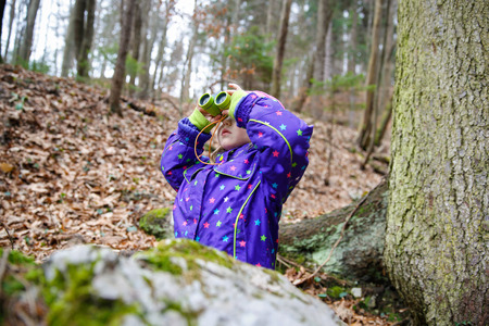 Girl scout looking through the binoculars in a forest, inspecting the surroundings and bird watching Stok Fotoğraf