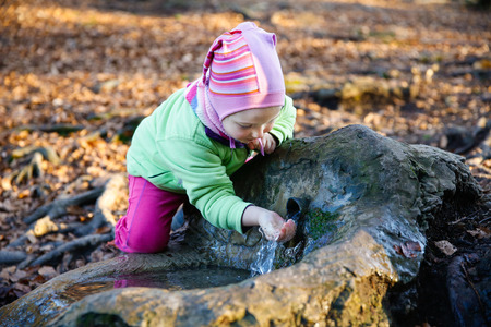 source of water: Adorable, thirsty little girl drinking clean spring water from a source in a forest Stock Photo