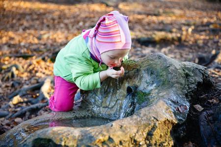 sediento: Adorable, ni�a sed bebiendo agua de manantial limpia de una fuente en un bosque