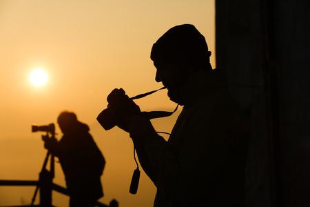 amateur: Silueta de fotógrafos tomando fotos de un sol increíble en la cima de una colina. Aficionados y profesionales que trabajan juntos.