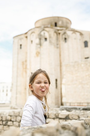 disobedience: Playful and carefree cute little Caucasian girl making faces, looking at mum and dad. Stock Photo