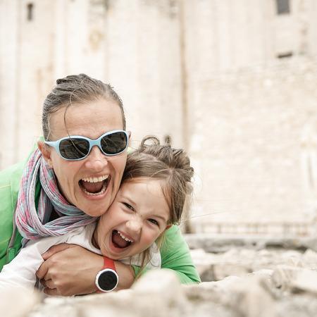 haciendo el amor: Madre Juguetón Europeo y abrazos hija, bromeando, haciendo muecas, sonriendo y divertirse viajar y disfrutar del verano. , Situación real Natural.