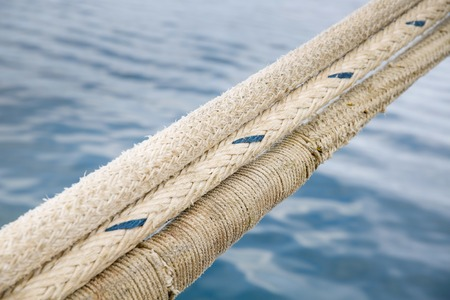 heavy duty: Heavy duty and weathered ropes, attached to the pier for secure docking of a ship. Maritime, nautical concept, background. Stock Photo