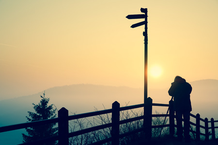 work experience: Silhouette of a photographer taking photos of an amazing sun at the top of a hill.
