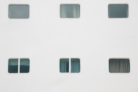 sightseeing tour: Cabin windows of a big white cruise ship, docked in port for maintenance, refill of supplies and sightseeing tour for passengers. Travel, hospitality, cruising business concept and background.